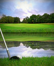 Hitting golf ball over water hazard Royalty Free Stock Photo