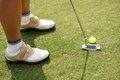 Hitting with putter cropped image of female golf player ball a Royalty Free Stock Images