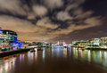 Hms belfast on river thames floodlit tower bridge and tower of london with reflections in the water Stock Photography