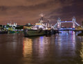 Hms belfast on river thames floodlit tower bridge and tower of london with reflections in the water Royalty Free Stock Photos