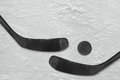 Hockey puck and a pair of black sticks on the ice Royalty Free Stock Photo