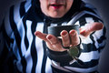 Hockey referee hold a puck in his palm close view Stock Photos