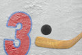 Hockey stick puck and the numeral three painted on ice Stock Photos