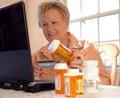 Hogere vrouw die tot geneeskunde online opdracht geeft Stock Foto
