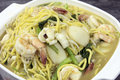 Hokkien mee stir fry yellow noodles with prawns squids fishcake and green vegetables top view closeup Royalty Free Stock Photos