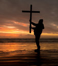 Hold up cross man holding a at sundown Stock Image