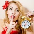 Holding alarm clock beautiful glamor young blond pinup woman in red dress showing silence sign looking at camera on white Royalty Free Stock Photos