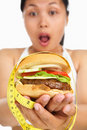 Holding burger with measuring tape around Stock Photo