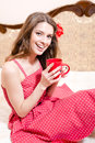 Holding cup of hot drink beautiful girl in red dress having fun relaxing in bed happy smiling & looking at camera Royalty Free Stock Photo