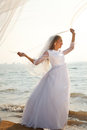Holding flying veil happy bride is standing on the beach and her Stock Images
