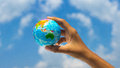 Holding a globe person with clouds in the background Royalty Free Stock Photos