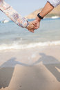 Holding hands couple on beach with shadow. Royalty Free Stock Photo