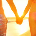 Holding hands couple in love relaxing on beach swimwear at rear view of fit s buttocks and legs as weight loss concept at sunset Stock Photo