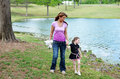Holding hands mother walking her daughter along a river bank Royalty Free Stock Images