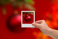 Holding instant photo christmas on a ball background Royalty Free Stock Images