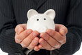Holding piggy bank man white over black suit background Royalty Free Stock Photos