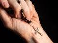 Holding rosary beads cross praying Stock Photo