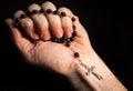 Holding rosary beads cross praying Royalty Free Stock Image