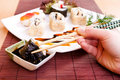 Holding sushi roll with chopsticks Stock Photo