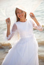 Holding a veil happy bride is standing on the beach and her flying Royalty Free Stock Photos