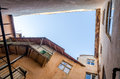 A hole in the sky in the roof collapsed in the old historic building with balconies, windows and entrance doors in the streets of Royalty Free Stock Photo