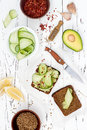Holewheat toast with avocado guacamole and cucumber slices. Breakfast with spicy avocado sandwiches on whole grain bread. Royalty Free Stock Photo