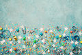 Holiday background decorated colorful confetti, star, candy and streamer on blue vintage table top view. Flat lay. Festive border.