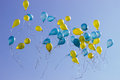 Holiday blue and yellow balloons in the blue sky Royalty Free Stock Photo