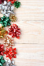 Holiday bows high angle image of a group of colorful on a white wood table vertical format with copy space Royalty Free Stock Image