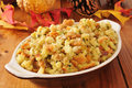 Holiday cornbread stuffing a small casserole dish of on a rustic wooden table with autumn leaves and pine cones Stock Image