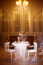 Holiday dinner table for two shined by classic chandelier light Royalty Free Stock Photo