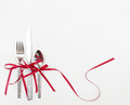 Holiday flatware with red ribbons christmas satin bows isolated on white background Royalty Free Stock Photo