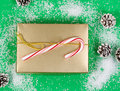 Holiday gift box on snowy green background high angle shot of golden candy cane and pine cones light Stock Photography