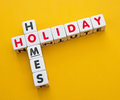 Holiday homes text and inscribed in uppercase letters on small white cubes arranged crossword style with common letter o yellow Royalty Free Stock Images