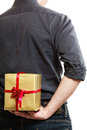 Holiday man hiding surprise gift box behind back and special occasion closeup of male hands giving golden with red ribbon isolated Royalty Free Stock Photo