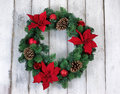 Holiday Poinsettia Christmas wreath on rustic white wooden board Royalty Free Stock Photo