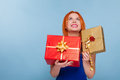 Holiday red haired happy girl with chrismas gift boxes looking up and occasion young holding golden xmas ribbon bow on blue Royalty Free Stock Photography