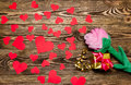 Holiday/romantic/wedding/valentine day background with plush rose, gift box, small hearts and gold ribbon on wooden table. Royalty Free Stock Photo
