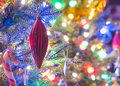 Holiday season, christmas tree decorations glow under luminous and vivid, colorful lights on a small faux indoor tree. Royalty Free Stock Photo