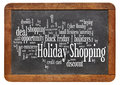 Holiday shopping word cloud consumerism concept on a vintage slate blackboard isolated on white Royalty Free Stock Photography