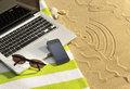 Holiday wifi laptop and cell phone on a beach towel with graphic in the sand Stock Image