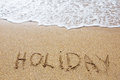 Holiday written in sand on the beach Royalty Free Stock Photos