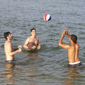 Holidays three adult men playing with ball in water Stock Image