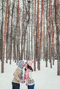 Holidays, winter, christmas, love and people concept - happy couple kissing in forest among fir trees in snow Royalty Free Stock Photo