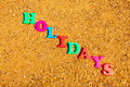 Holidays the word written in alphabet letters on a sand background Stock Image