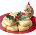 Holly christmas shortbread with santa an echidna wearing a cap look at the triangular pieces of decorated a sprig of on a red Royalty Free Stock Photography