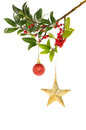 Holly gold star and bauble a berry laden bough decorated with a christmas Stock Photo