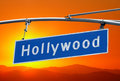 Hollywood blvd sign with bright orange sunset sky street and mountains Stock Image
