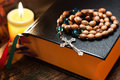 Holy bible with rosary beads on wooden background thin depth of field focus on cross Stock Photo