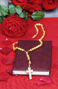 Holy bible rosary and stunning red roses on wooden table Royalty Free Stock Photos